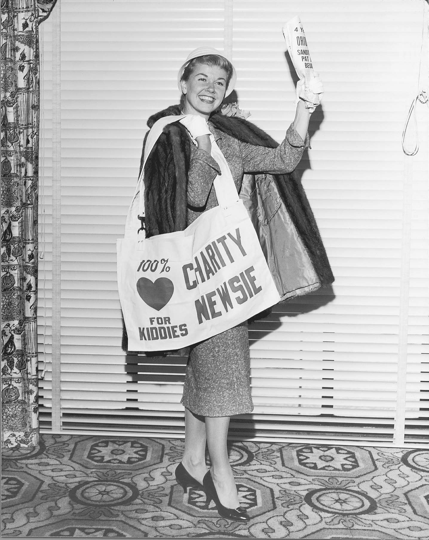 "Entertainer DORIS DAY in an undated black and white file photo. Source: Courtesy CHARITY NEWSIES . Doris was in Columbus when this was taken. She is holding a ""Charity Newsie"" newspaper bag and a copy of the paper. (Hoping to get more file photo info, date, context etc. from John Eberle.)"